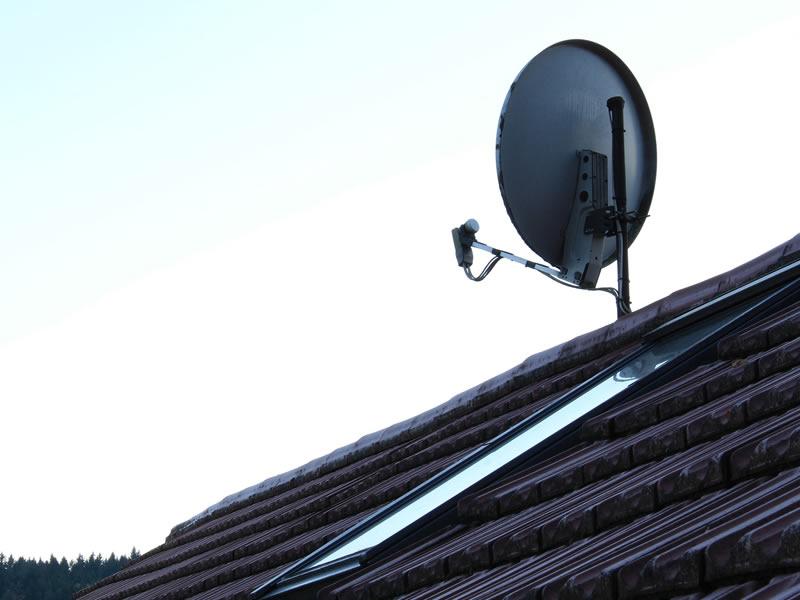 vista di un antenna parabolica sul tetto di un paese in provincia di bergamo